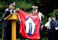 Police Chief Michael Wynn (left) and Fire Chief Robert Czerwinski drape a 9/11 commemorative flag over the podium before Wynn addressed county police, fire departments, and citizens in a ceremony at t